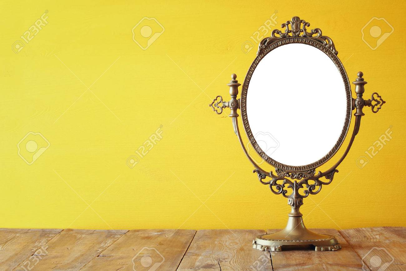 Old vintage oval mirror standing on wooden table. Stock Photo - 65644020