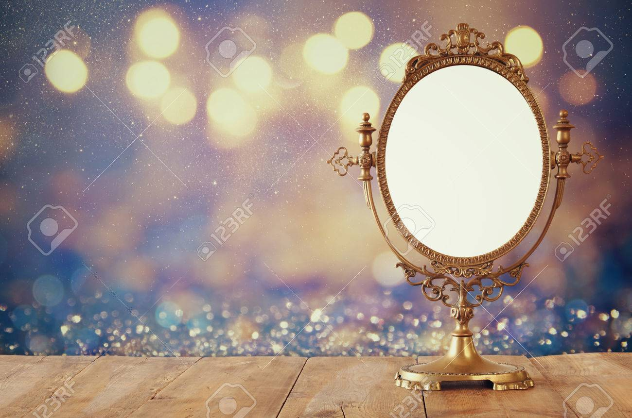 Old vintage oval mirror standing on wooden table. Stock Photo - 65645933