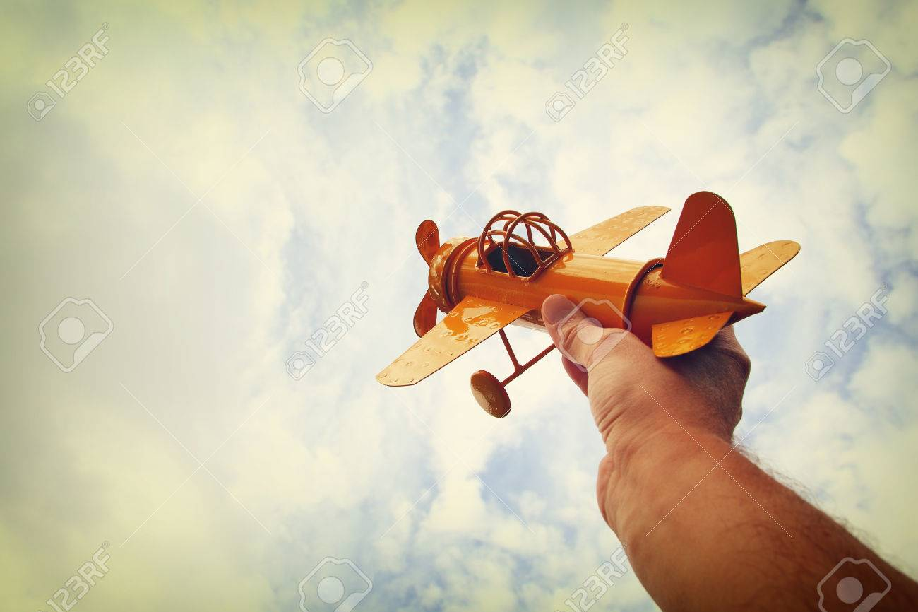 close up photo of man's hand holding retro airplane against blue sky. Filtered image Stock Photo - 66813295