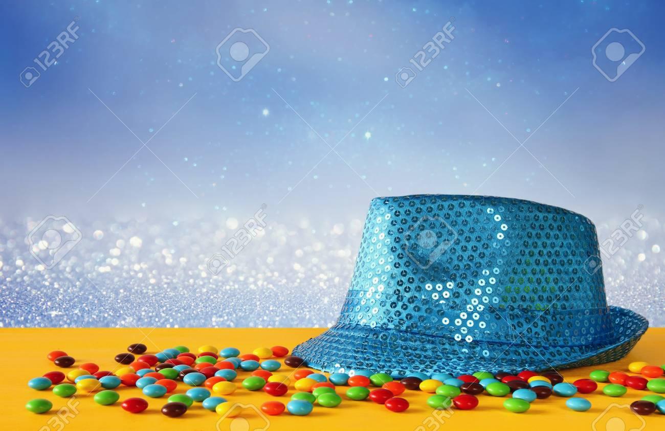 sélectionner pour l'original produits chauds sortie en ligne Chapeau bleu brillant du parti à côté de bonbons colorés sur le jaune table  en bois