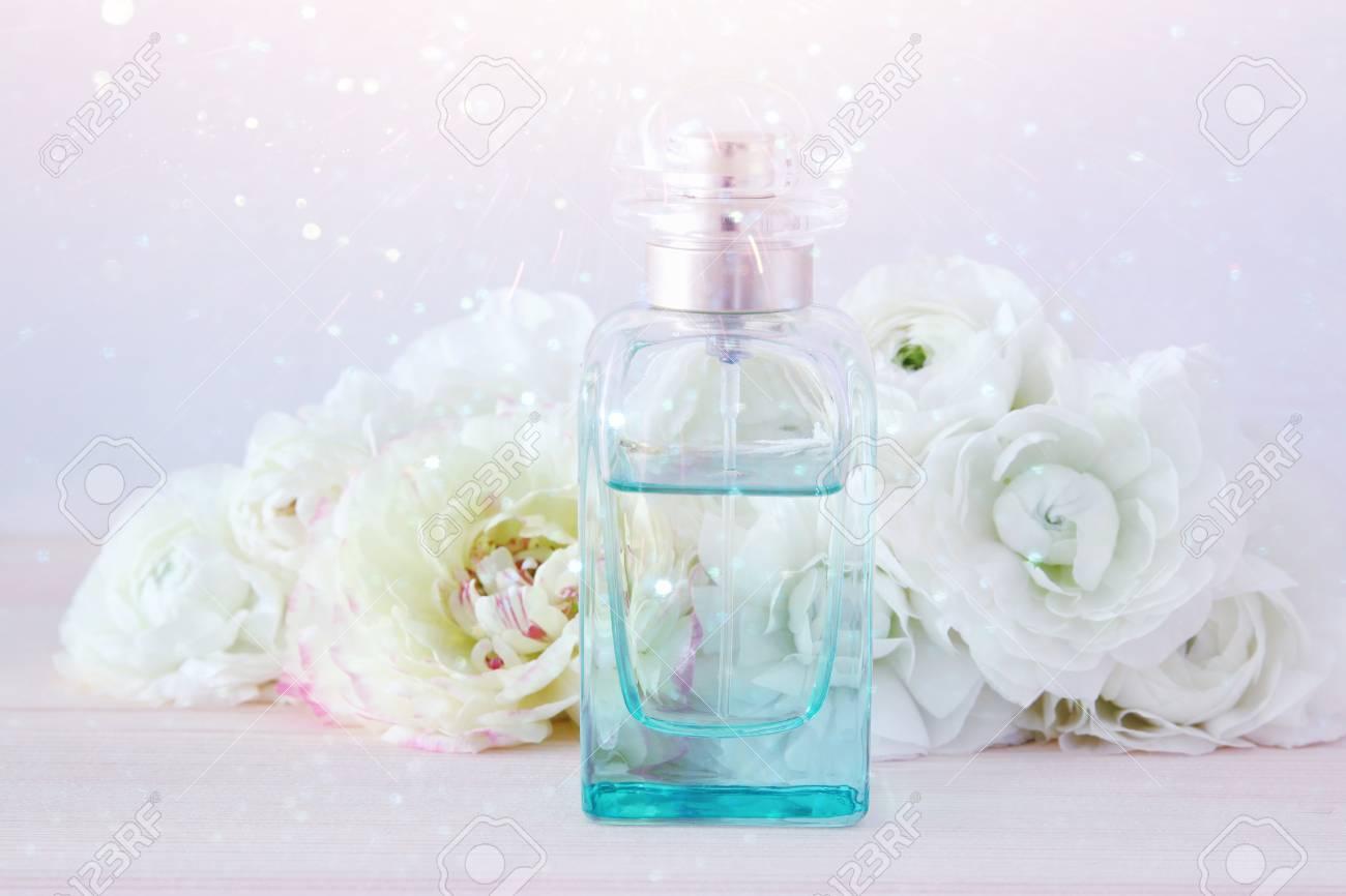 Perfume Bottle Next To Aromatic Flowers On White Table Stock Photo
