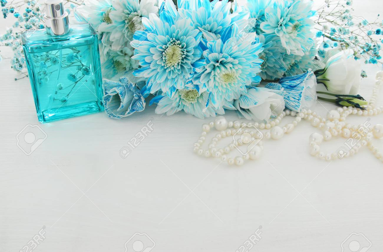 Top view of beautiful and delicate blue flowers arrangement next stock photo top view of beautiful and delicate blue flowers arrangement next to pearls necklace and fresh perfume on white wooden background copy space izmirmasajfo