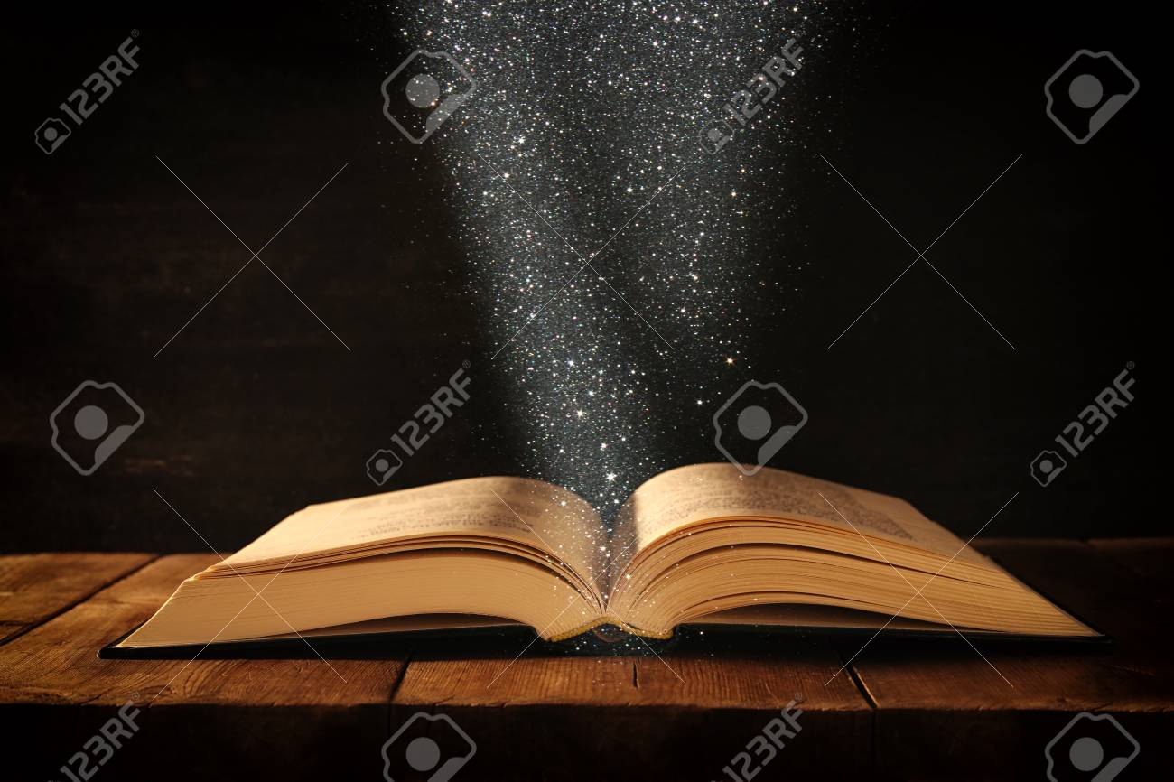 image of open antique book on wooden table with glitter overlay - 90442158