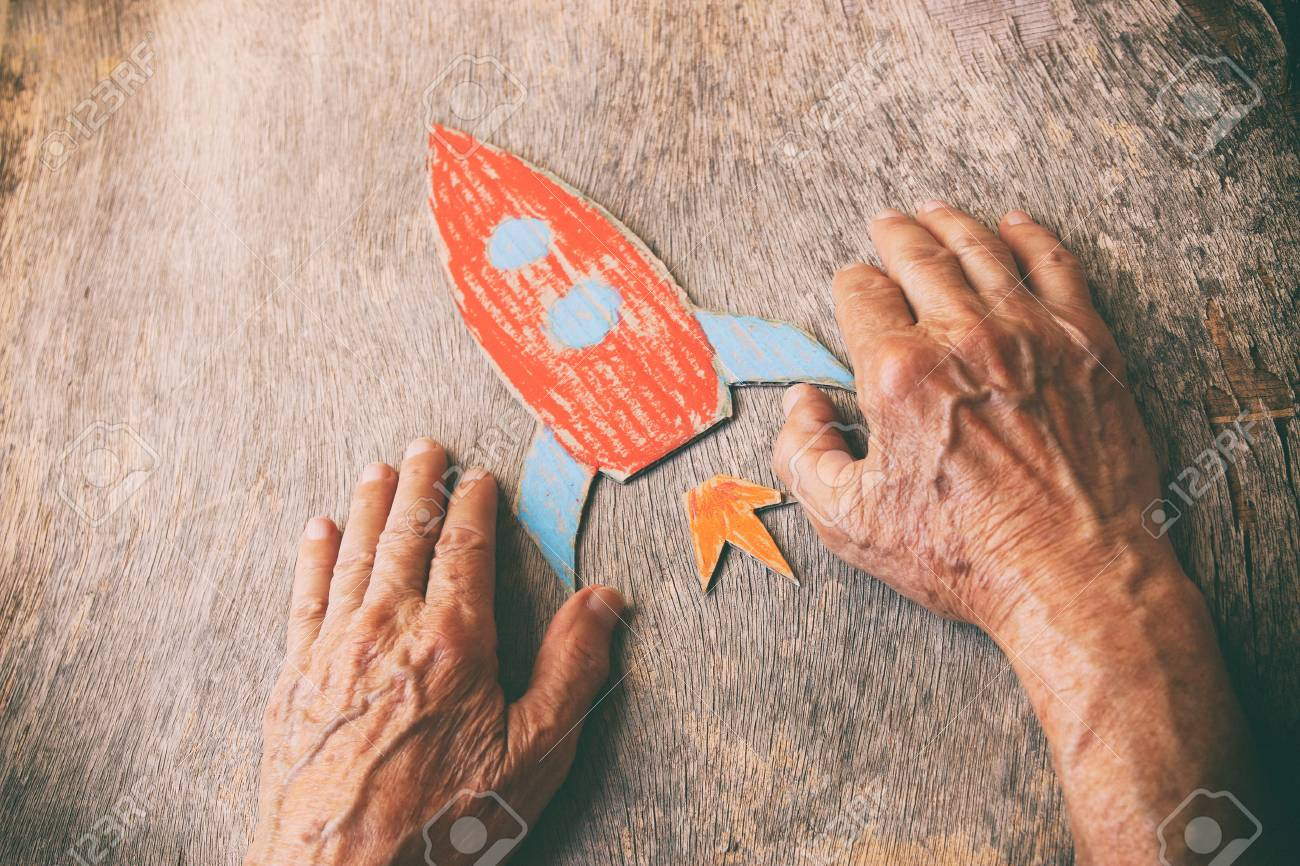 A close up of an elderly man holding a paper rocket on a wooden table. Concept of thinking about childhood dreams, sadness and loneliness. - 103510736