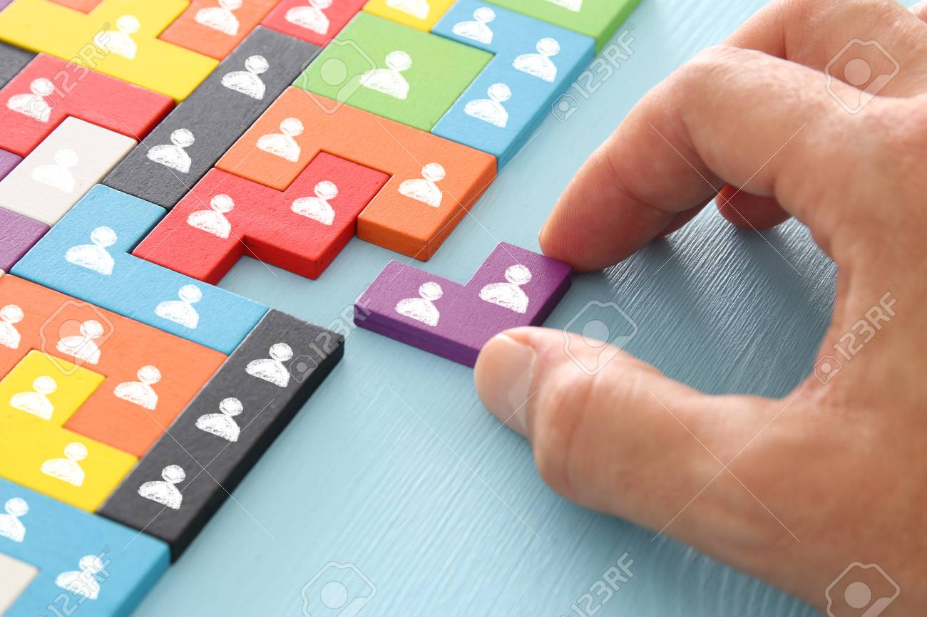 image of tangram puzzle blocks with people icons over wooden table ,human resources and management concept - 105463057