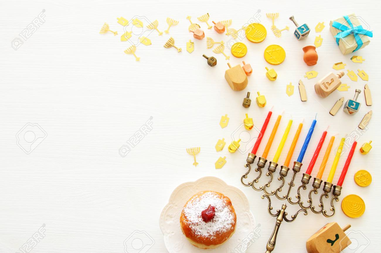 Top view image of jewish holiday Hanukkah background with traditional spinnig top, menorah (traditional candelabra) and candles - 110527322