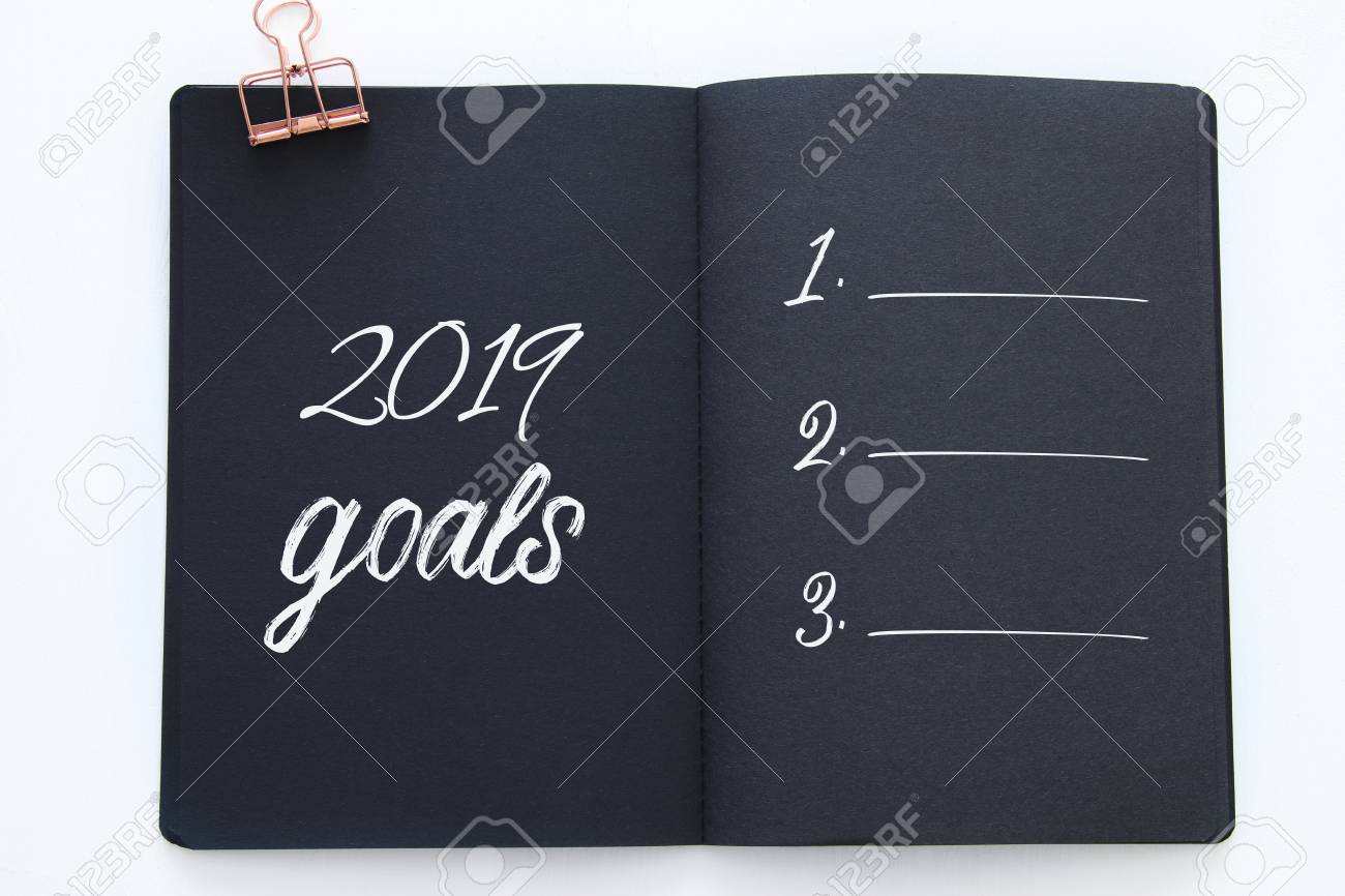 Top view 2019 goals list with notebook over wooden white desk - 111522517