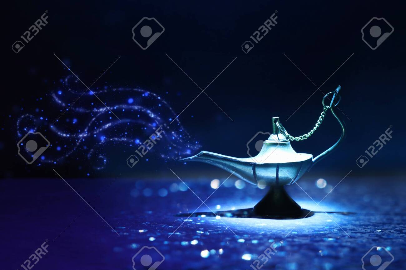 Image of magical mysterious aladdin lamp with glitter smoke. Dark background and dramatic light - 124058154