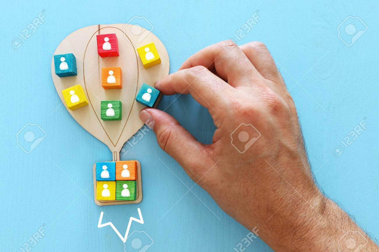 Business image of wooden air balloon with people icons over blue table, human resources and management concept - 126463640