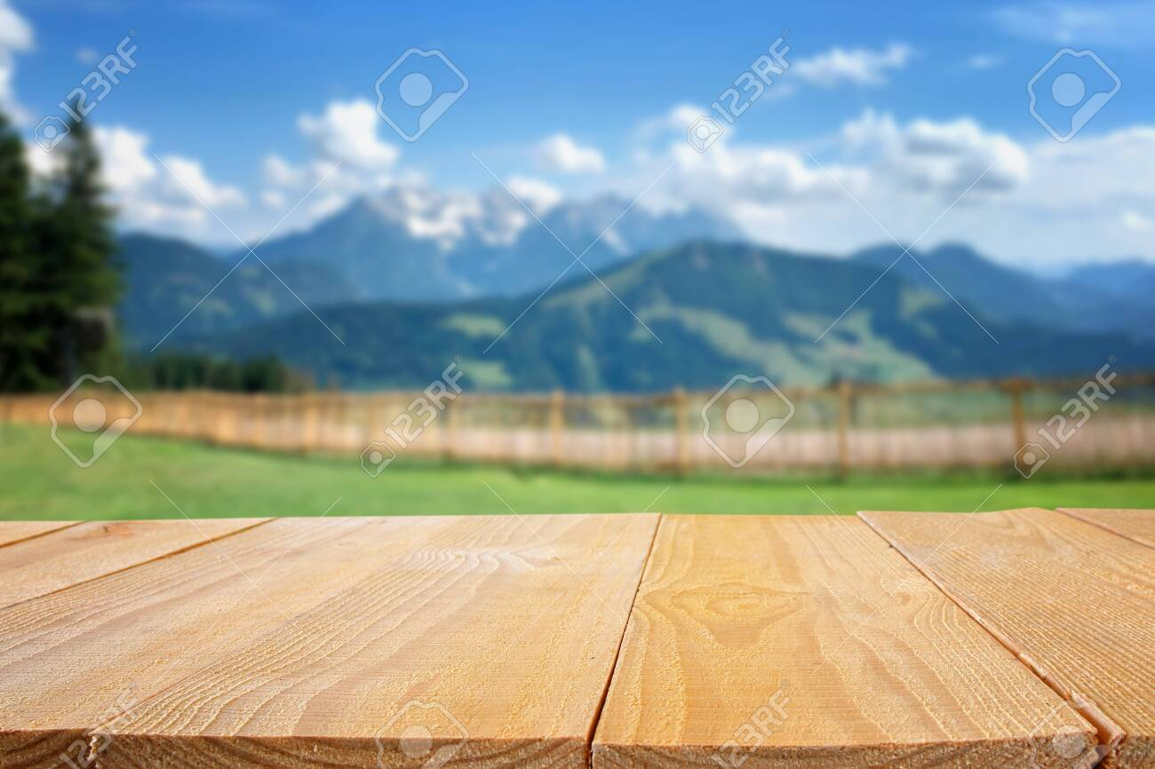 Empty table in front of blurry nature and mountains background. Ready for product display montage - 126835940