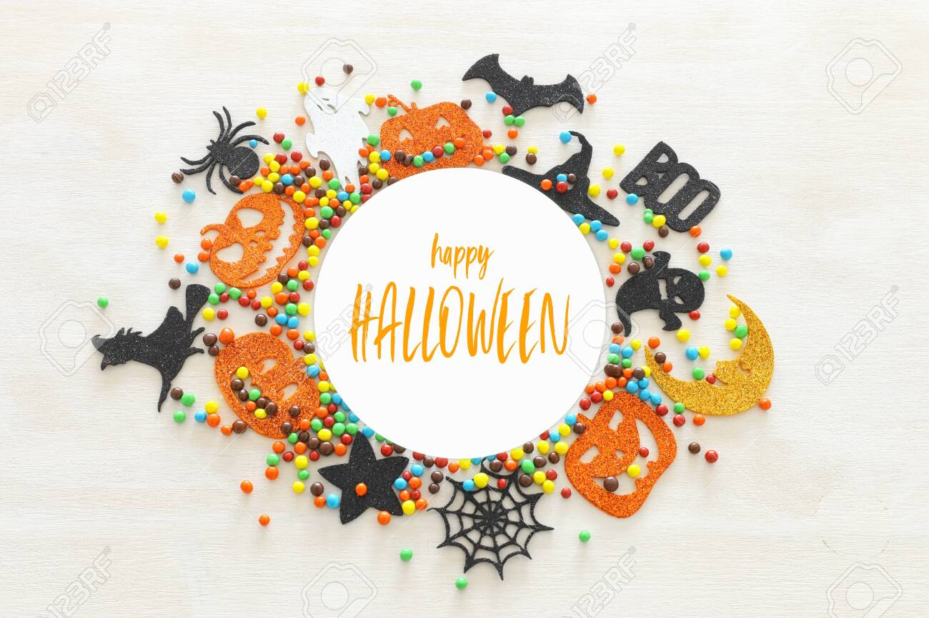 holidays image of Halloween. Pumpkins, bats, treats, bat and witch over white wooden background. top view, flat lay - 128926081