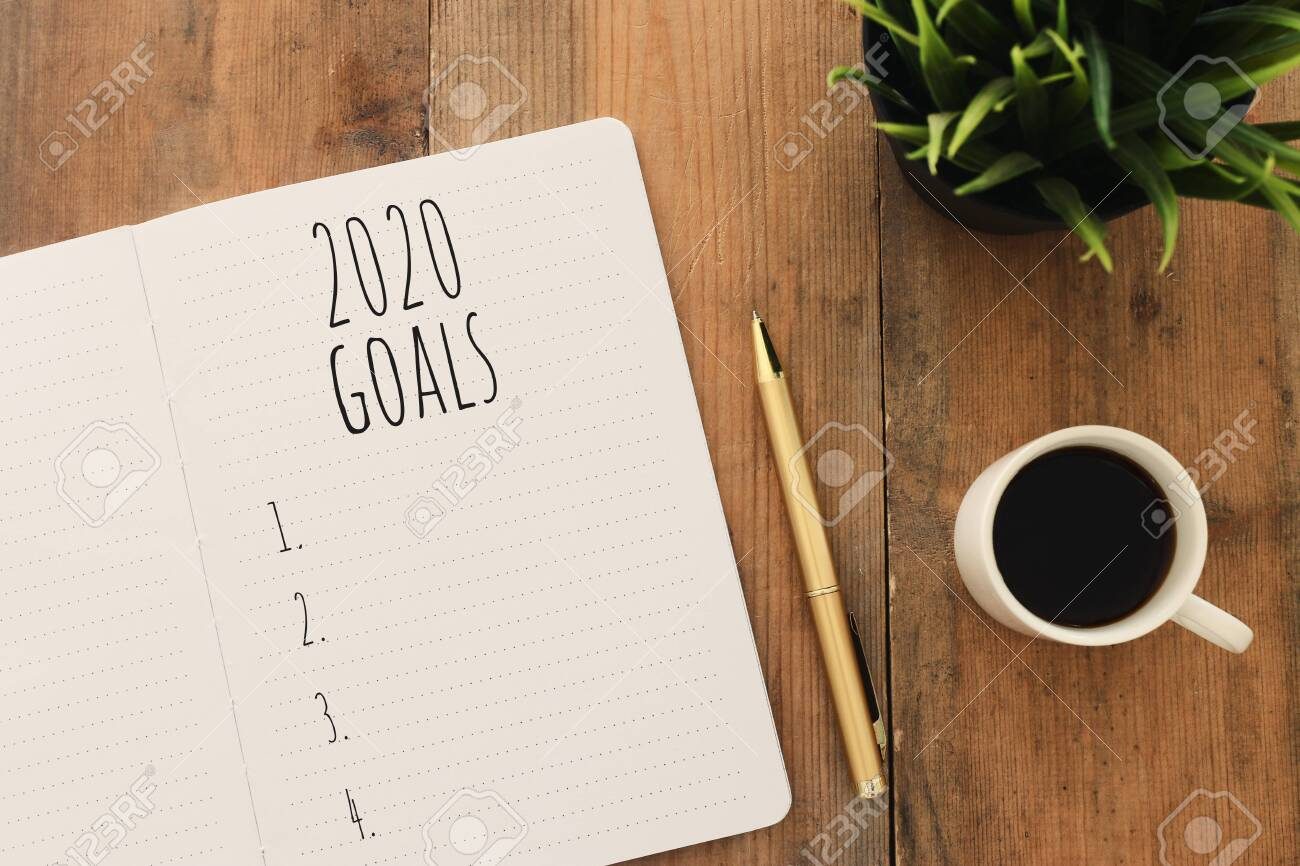 Business concept of top view 2020 goals list with notebook, cup of coffee over wooden desk - 132602091