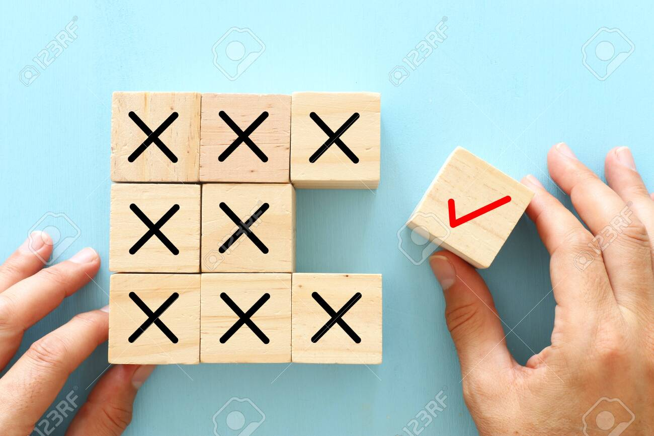 A hand chooses a cube with check mark symbol instead of cubes with cross sign. An idea of positive thinking and change of mind - 135242450