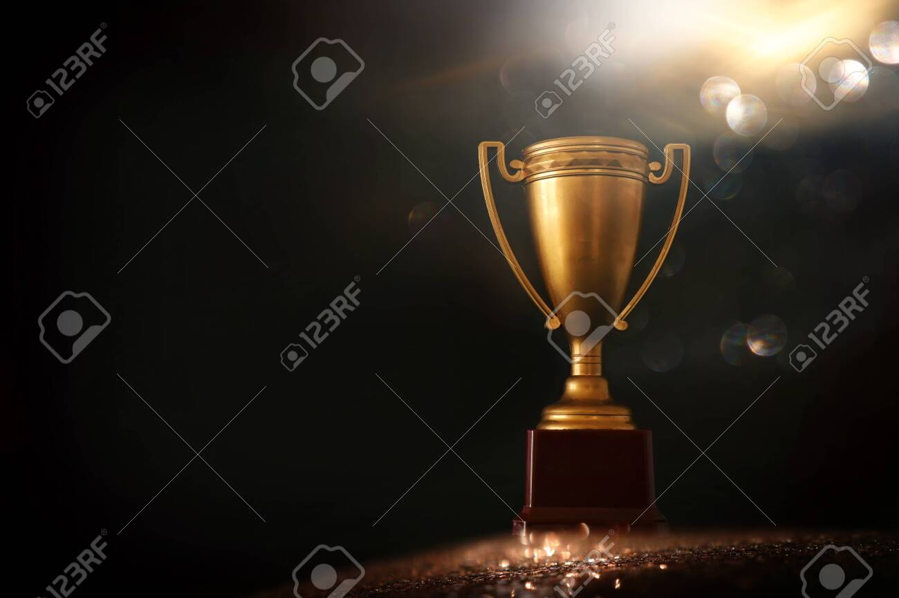 low key image of trophy over wooden table and dark background, with abstract shiny lights - 137390466