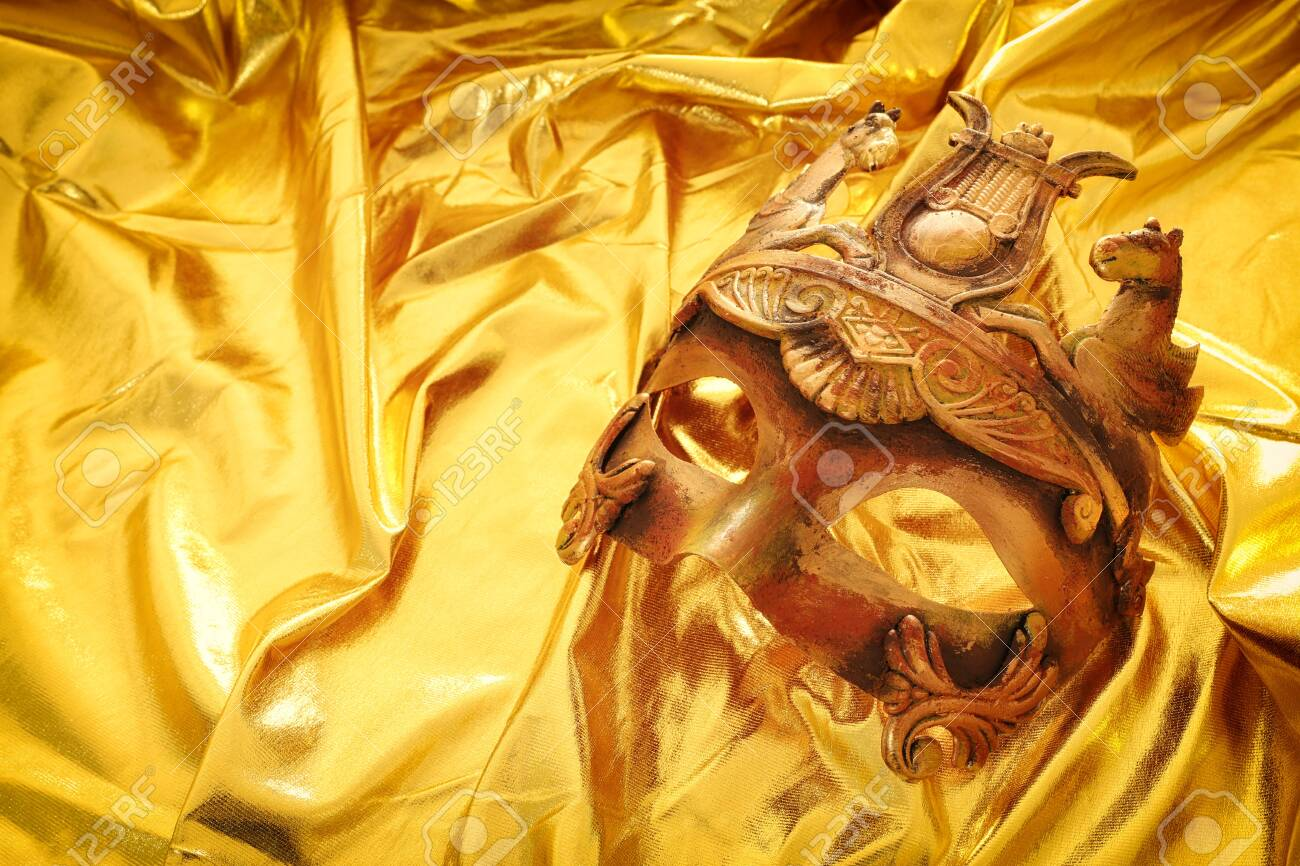 Photo of elegant and delicate Venetian mask over gold silk background - 139025254