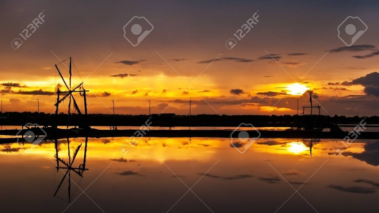 Beautiful sunset view of salt farm and wind wheel in Thailand Stock Photo - 16798931