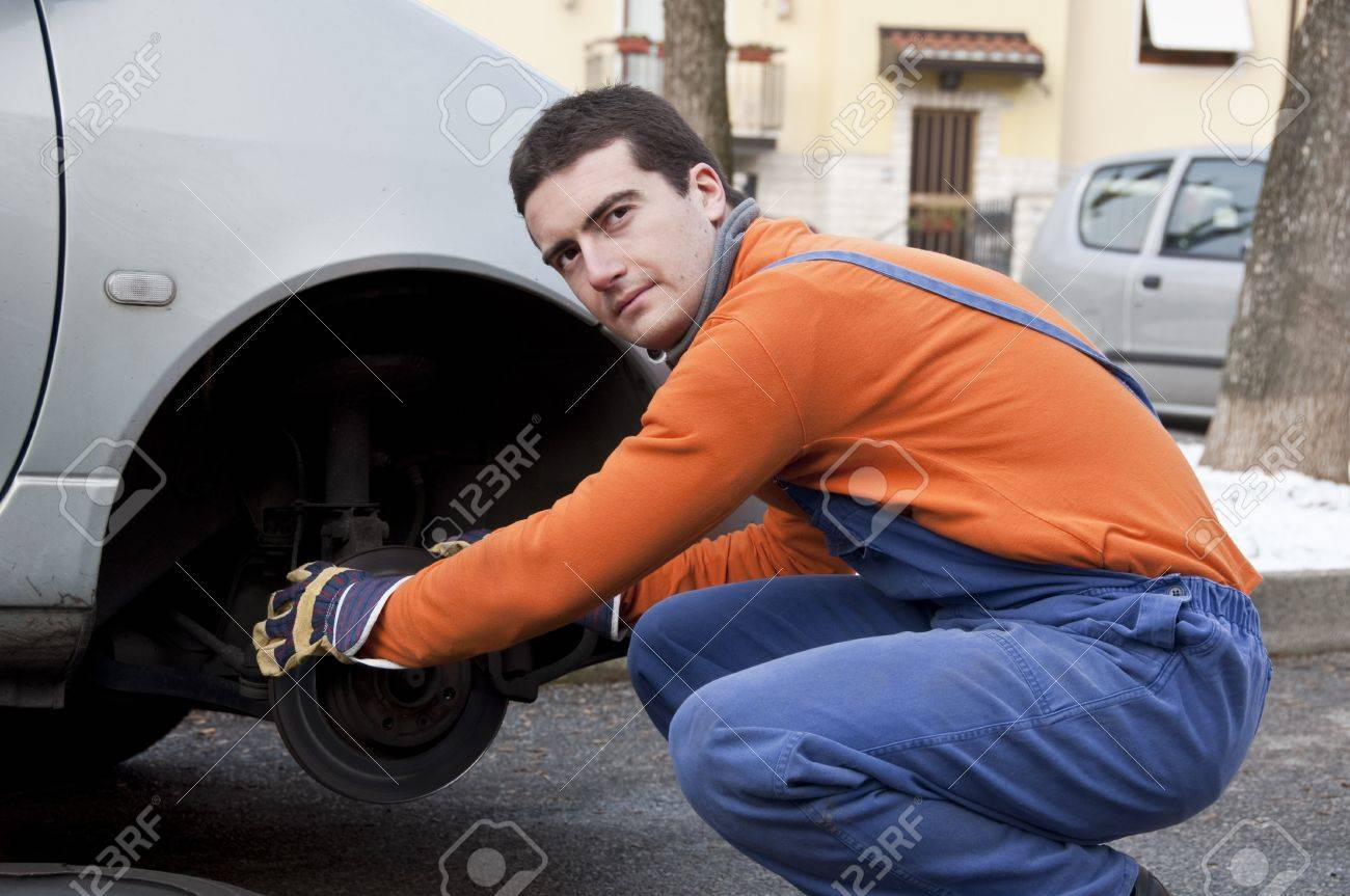 mechanic checking car brakes Stock Photo - 12897479