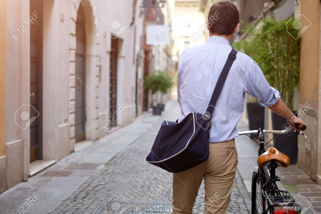 Picture of a young smiling business man on a bicycle on his way home from work while the sun is setting. He has a more relaxed style with the sleeves of his blue shirt rolled up and he is also wearing a blue bag on his shoulder. In the background there's - 58411124
