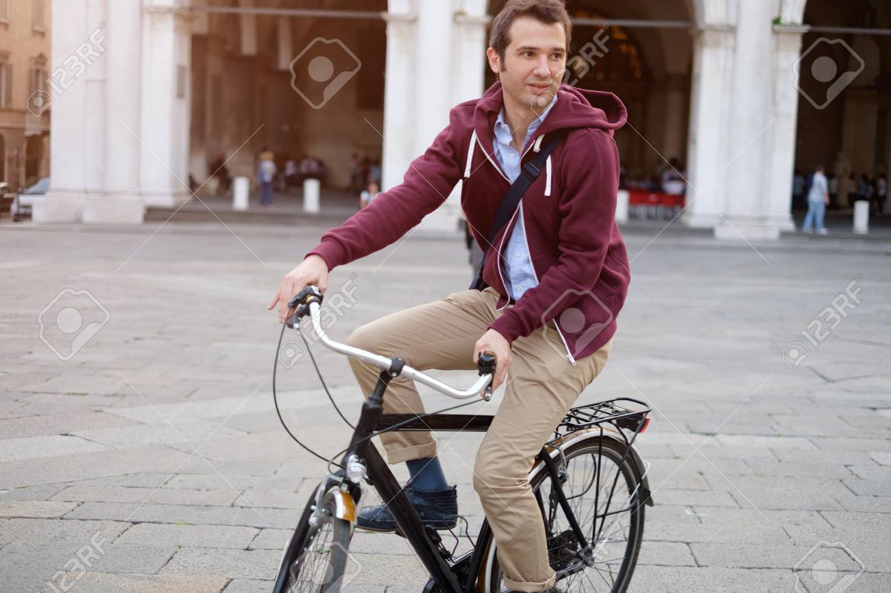 Picture of a young student man on a bicycle on his way home from work while the sun is setting. He has a more relaxed style . In the background there's a city square with some city buildings. - 58411137