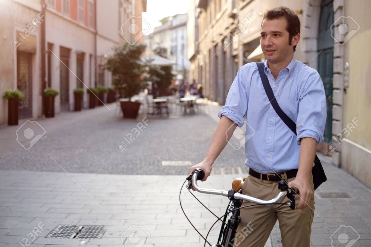 Picture of a young smiling business man on a bicycle on his way home from work while the sun is setting. He has a more relaxed style with the sleeves of his blue shirt rolled up and he is also wearing a blue bag on his shoulder. In the background there's - 58411139