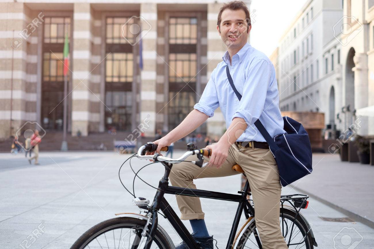 Picture of a young smiling business man on a bicycle on his way home from work while the sun is setting. He has a more relaxed style with the sleeves of his blue shirt rolled up and he is also wearing a blue bag on his shoulder. In the background there's - 58411146