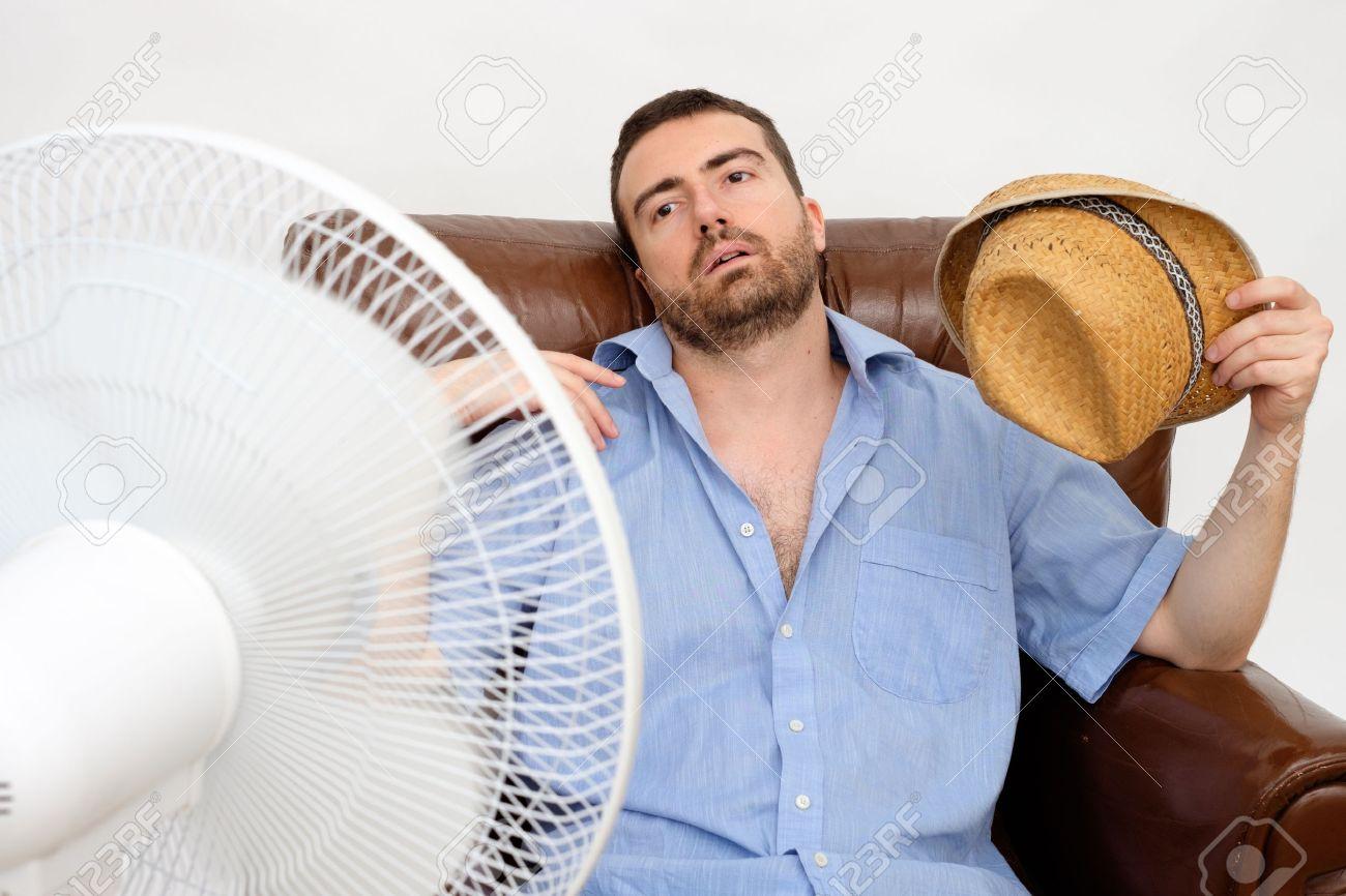 Flushed man feeling hot in front of a fan - 61517982