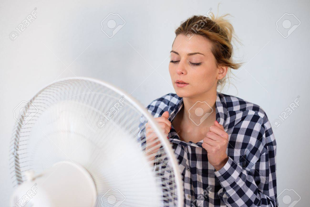 Girl face expression cooling in front of a fan - 88760547