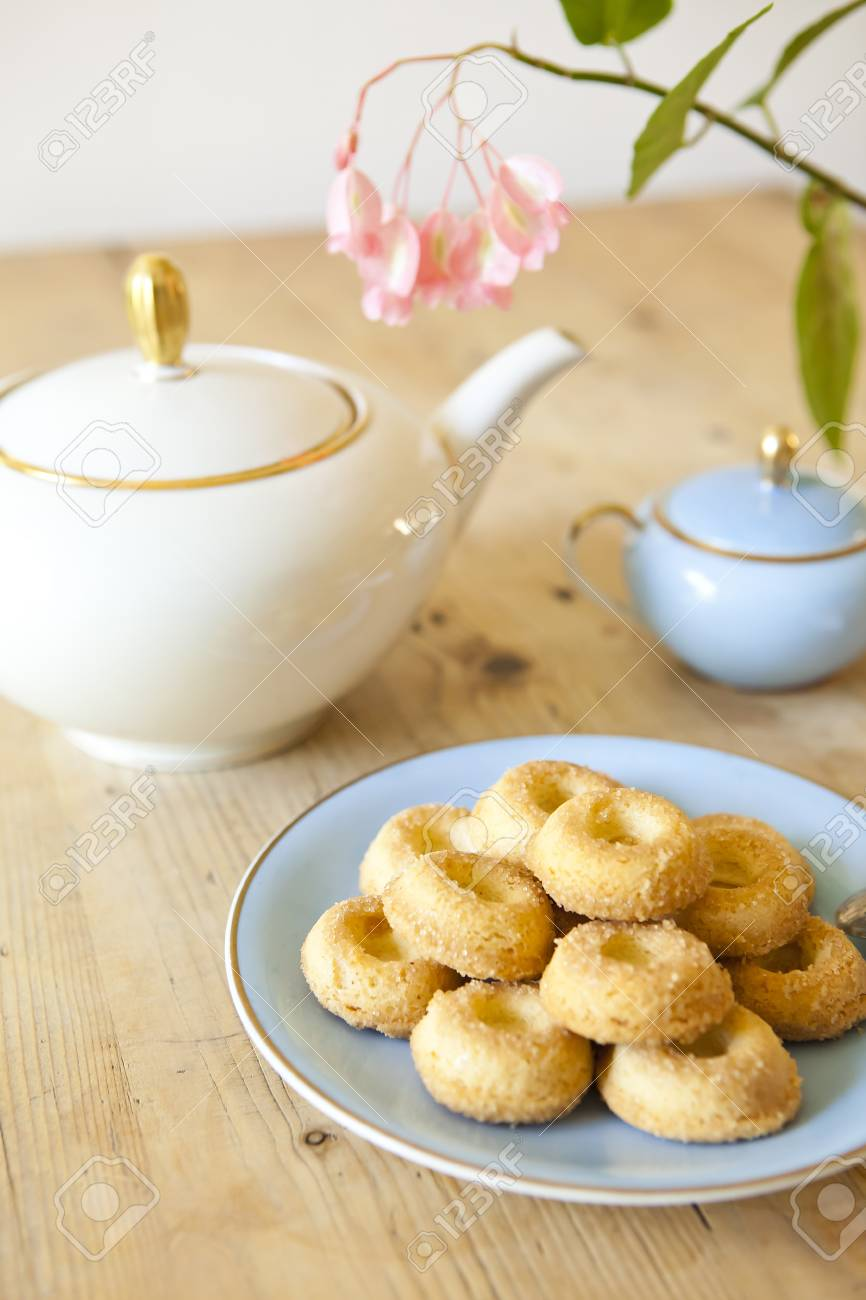 a plate of biscuits, a tea pot and a flower on wooden table Stock Photo - 15528647