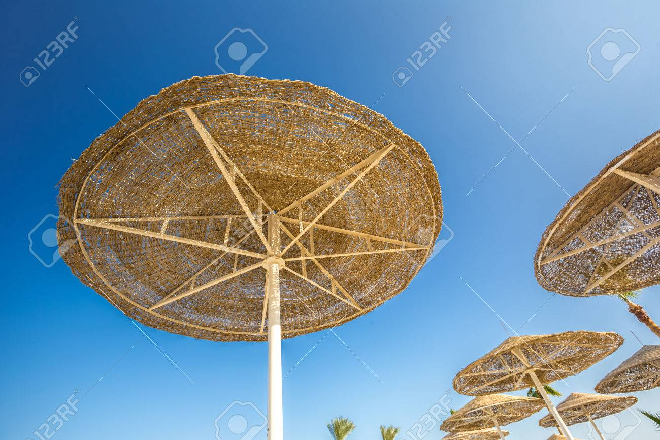 guardando una grande ombrelloni o tende di paglia su un rack