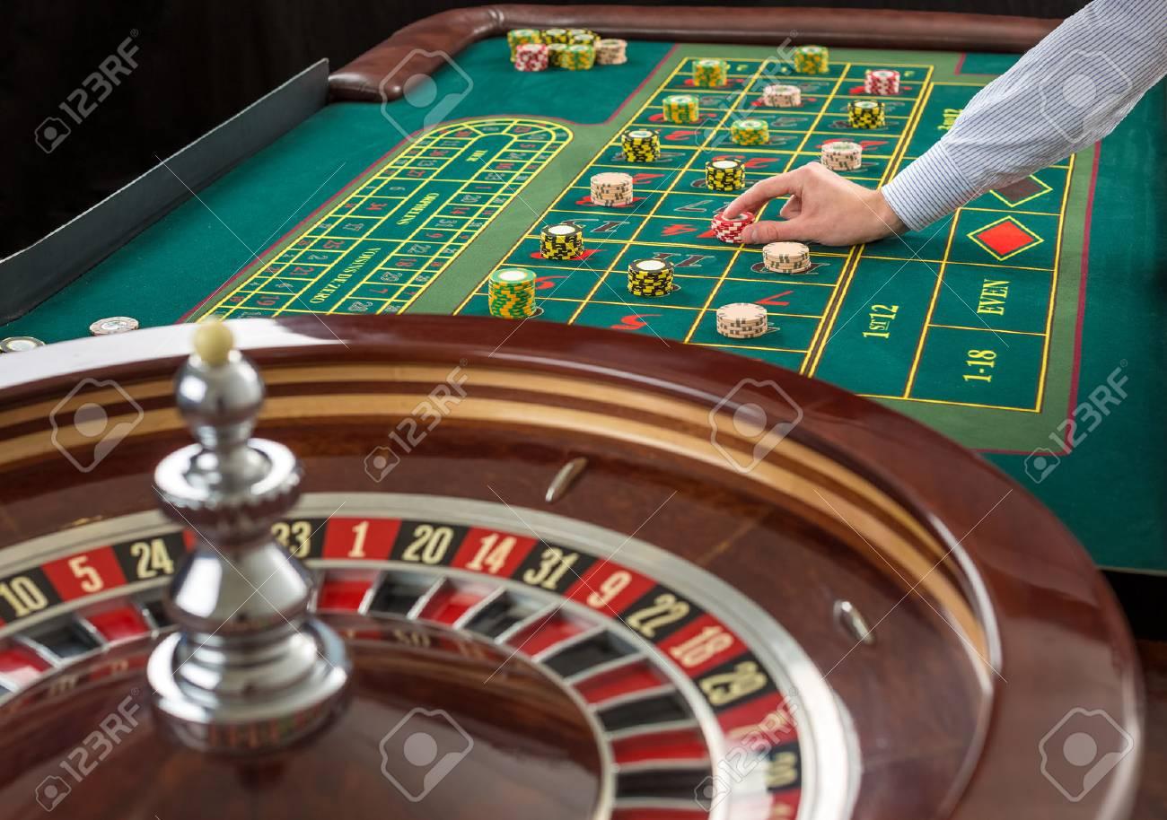 Nahaufnahme von Roulette und Haufen von Spielmarken auf einem grünen Tisch im Casino. Man Hand über Casino Chips auf Roulette Tisch