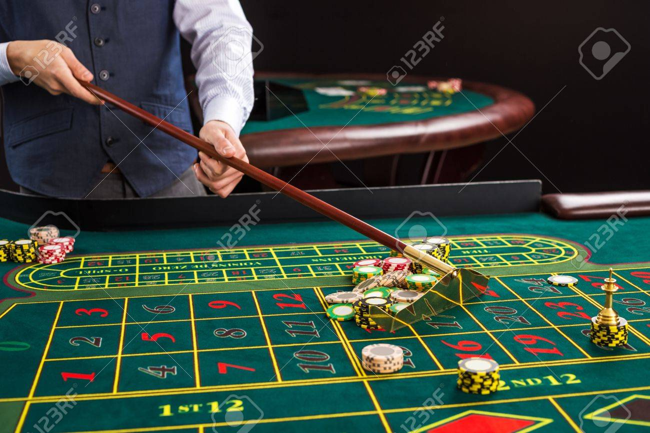 Gambling Chips On A Green Table In Casino. Croupier Collects.. Stock Photo, Picture And Royalty Free Image. Image 51965755.