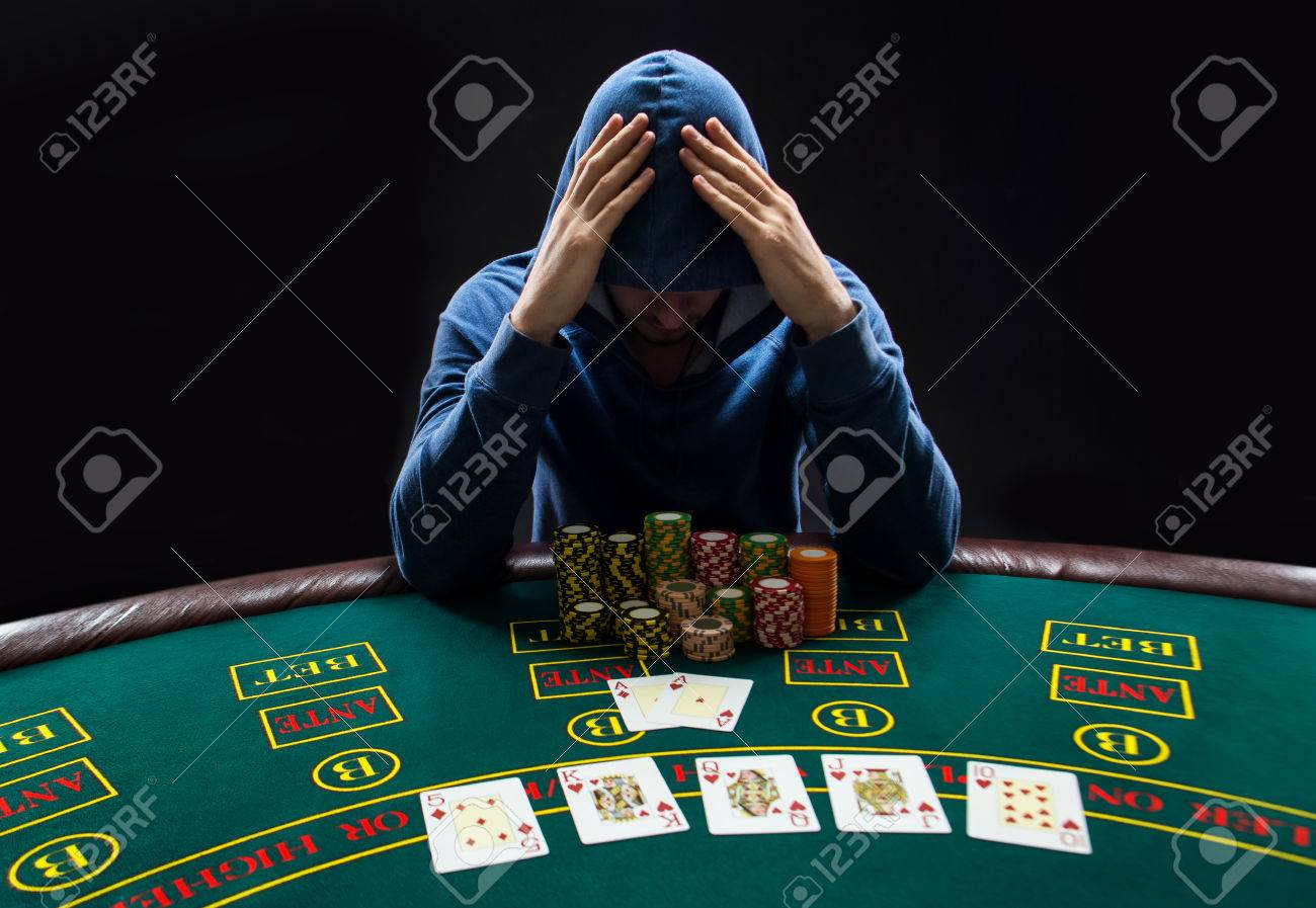 Portrait Of A Professional Poker Player Sitting At A Poker Table With Poker  Chips Trying To