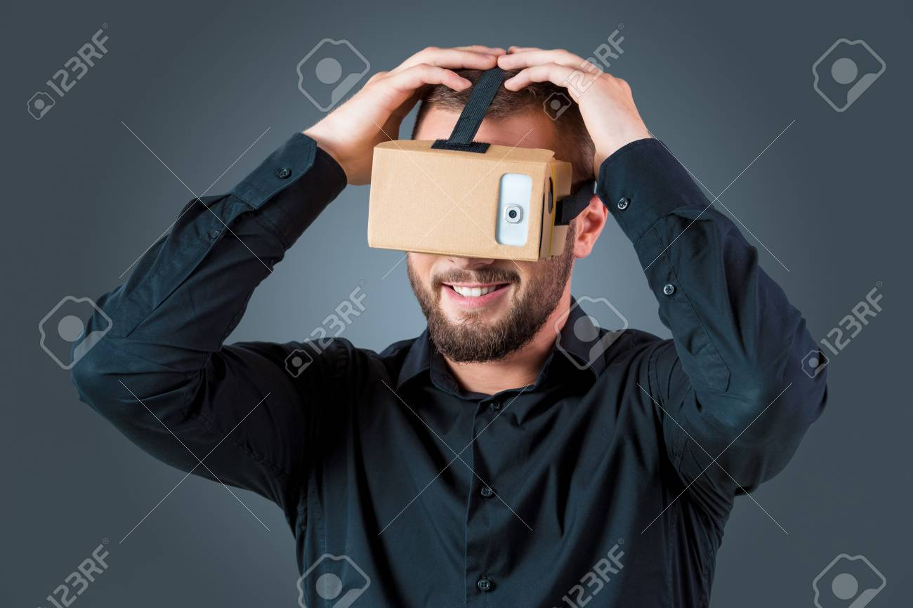 7fbf60e2c4a8 Excited young man using a VR headset glasses and experiencing virtual  reality on grey blue background