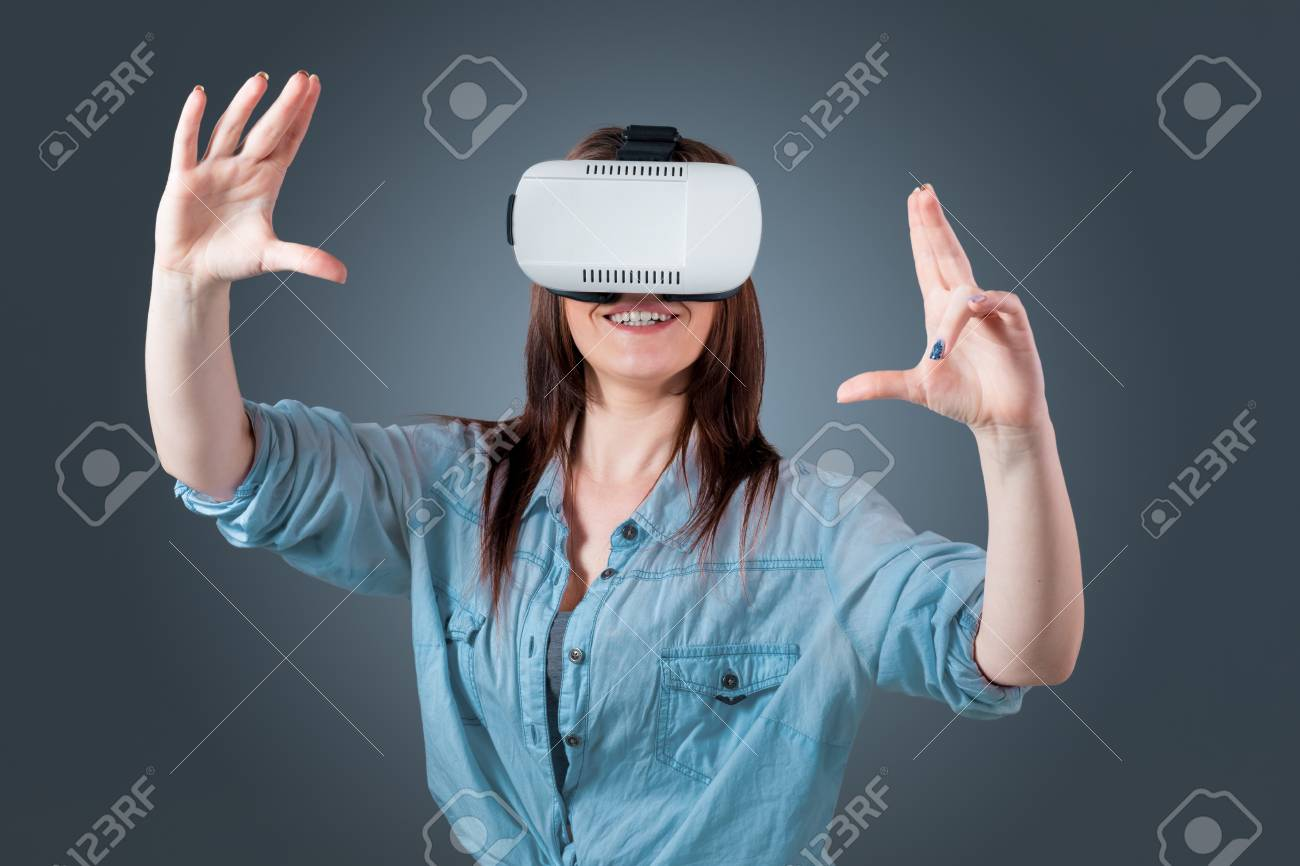 06576522e7fd Excited young woman using a VR headset glasses and experiencing virtual  reality on grey blue background