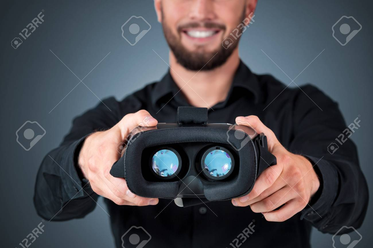 cc290cfa4b55 Excited young man using a VR headset and experiencing virtual reality on grey  blue background.