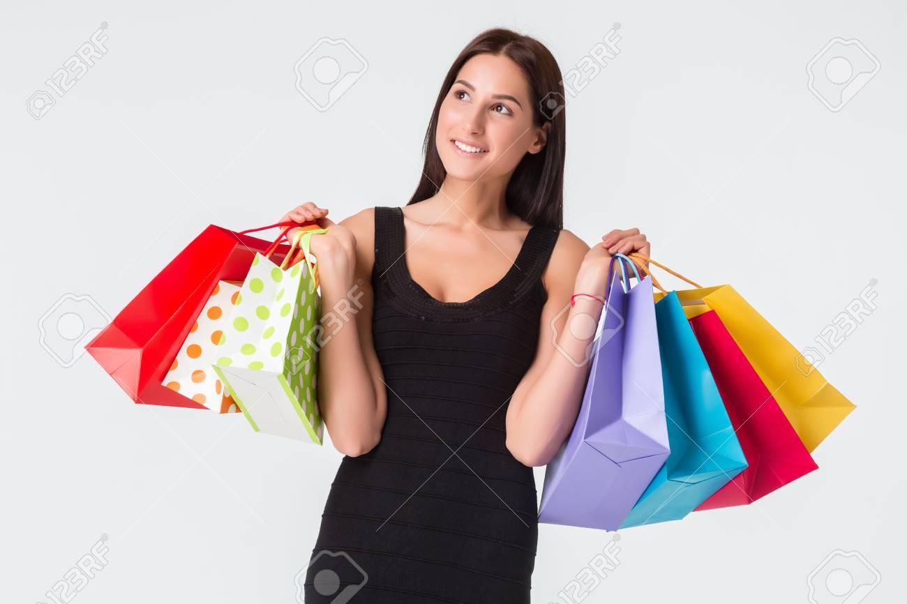 Feliz sonriente mujer joven con bolsas de compras después de ir de compras. La morena en un vestido negro, aislado en fondo blanco