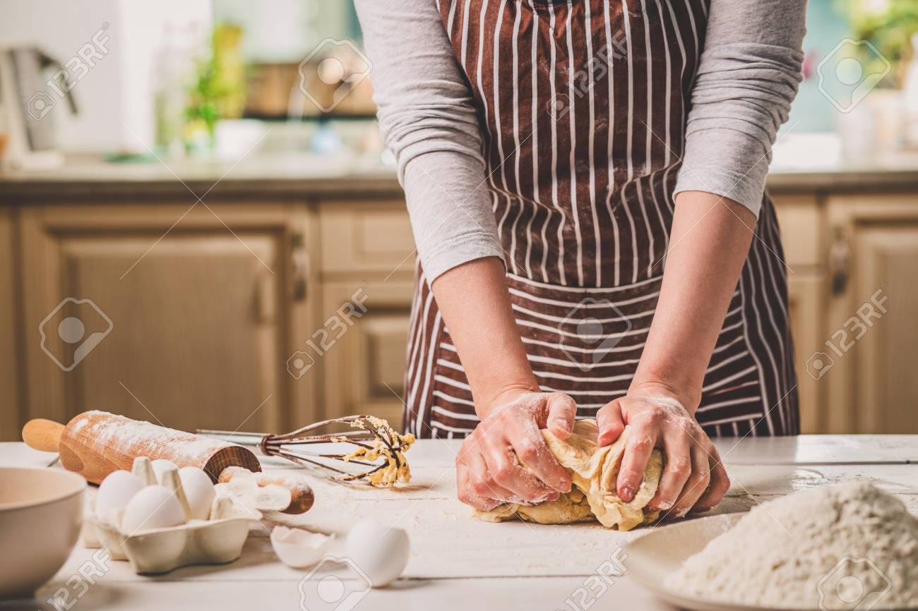 Manos de mujer amasando la masa en la mesa de la cocina. Una mujer en un  delantal a rayas está cocinando en la cocina