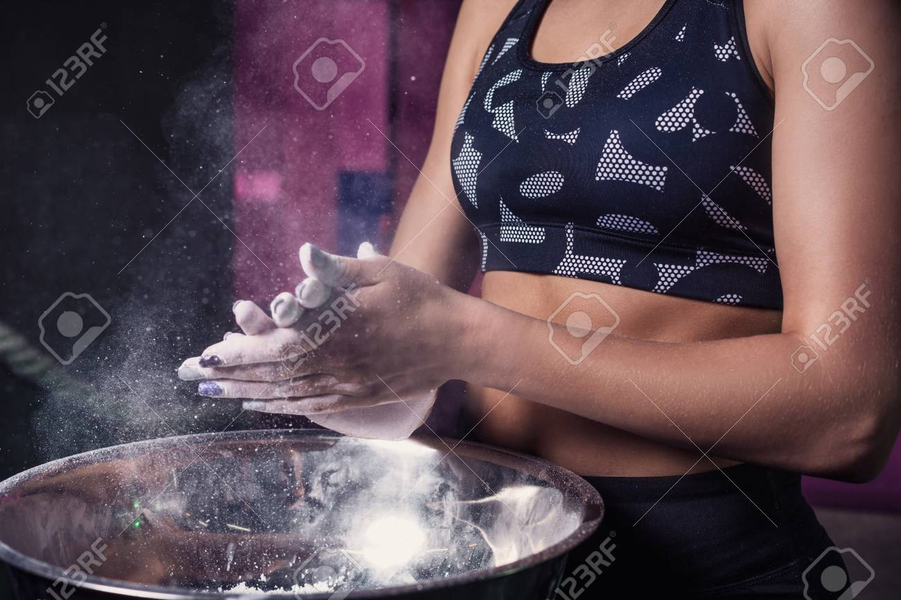 Female fitness model clapping hands with talc powder in a gym