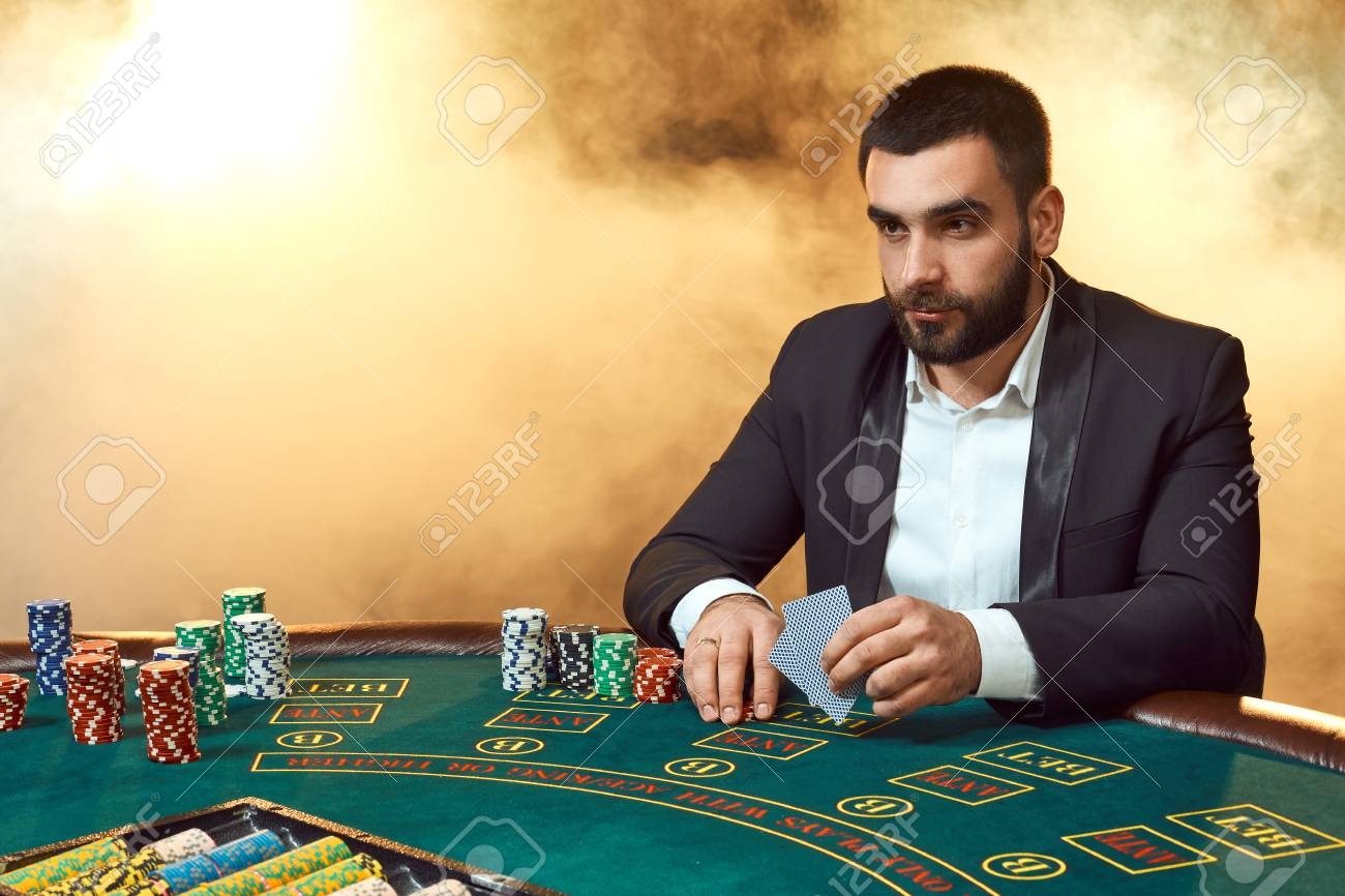 A Young Man In A Business Suit Sitting At The Poker Table. Man.. Stock  Photo, Picture And Royalty Free Image. Image 95766035.
