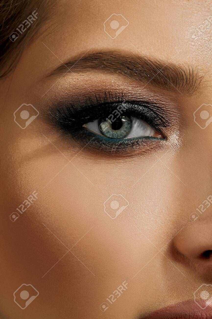 Face of lady with luxury makeup. Gray eyeshadow, long eyelashes, matte beige lips, brown eyebrows. Professional maquillage. Close up - 144651283