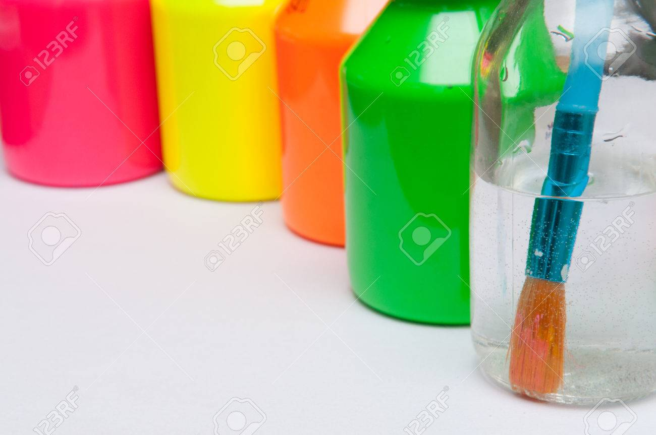 Paint Brush In Water In Front Of Brightly Coloured Childrens.. Stock ...