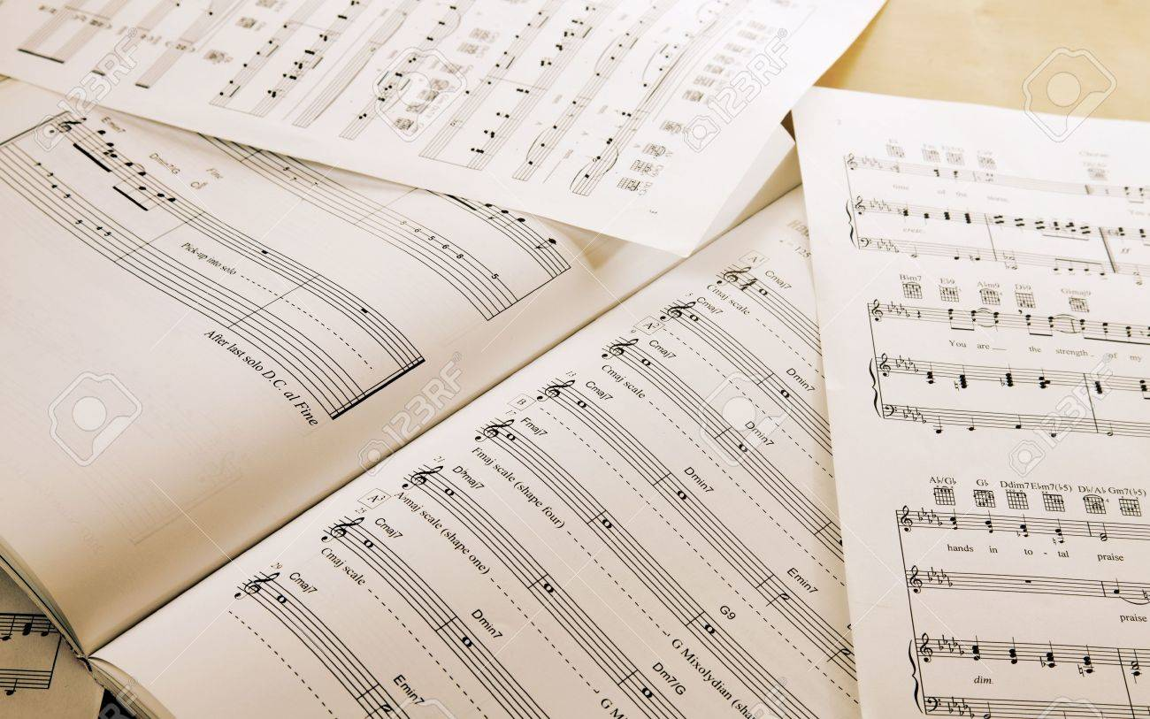Book and papers with music notes on table Stock Photo - 10492052