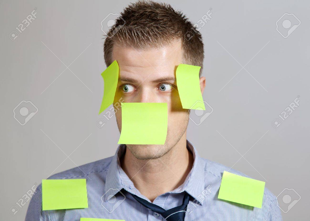 Confused businessman with post it notes on face and clothes Stock Photo - 13131271
