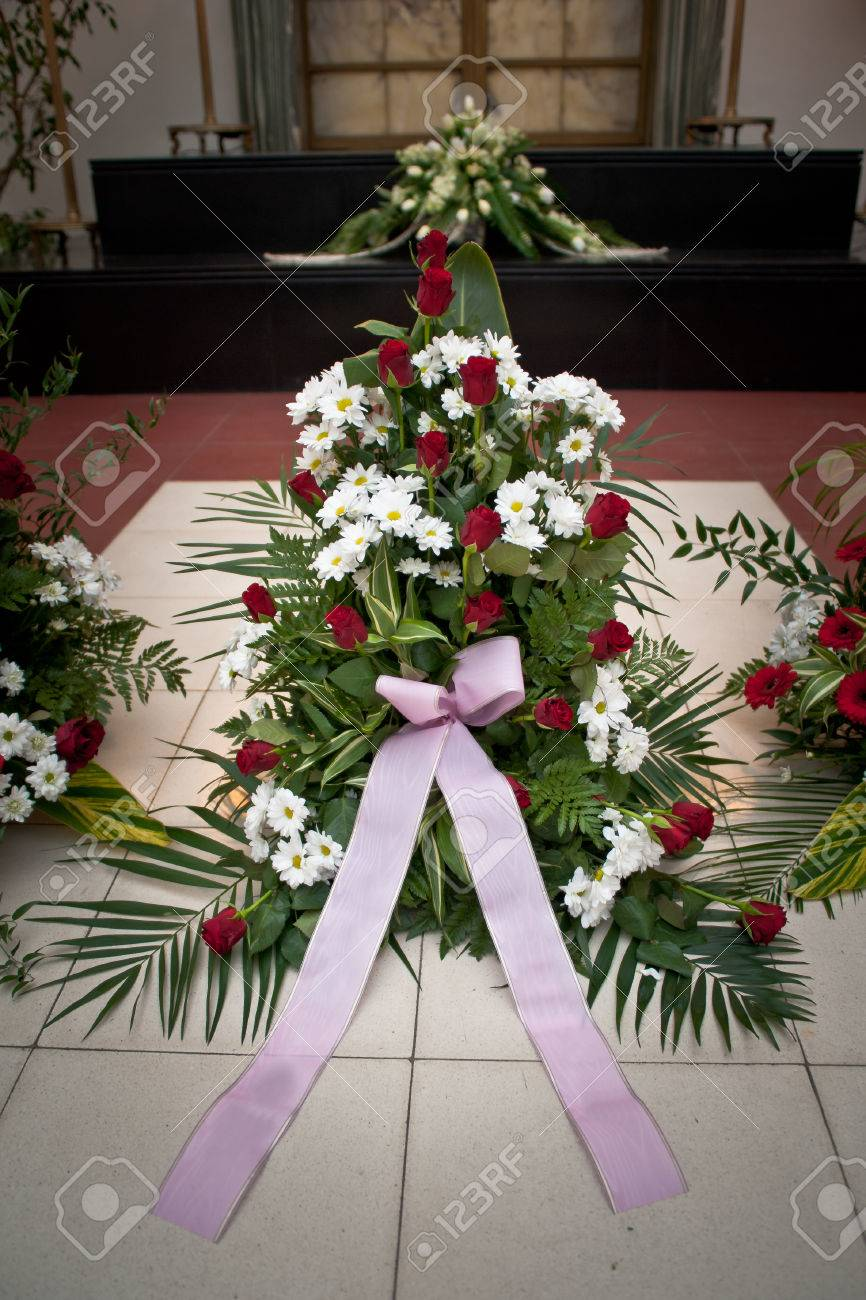 Large Funeral Flowers In Wreath With Ribbon On Floor Stock Photo