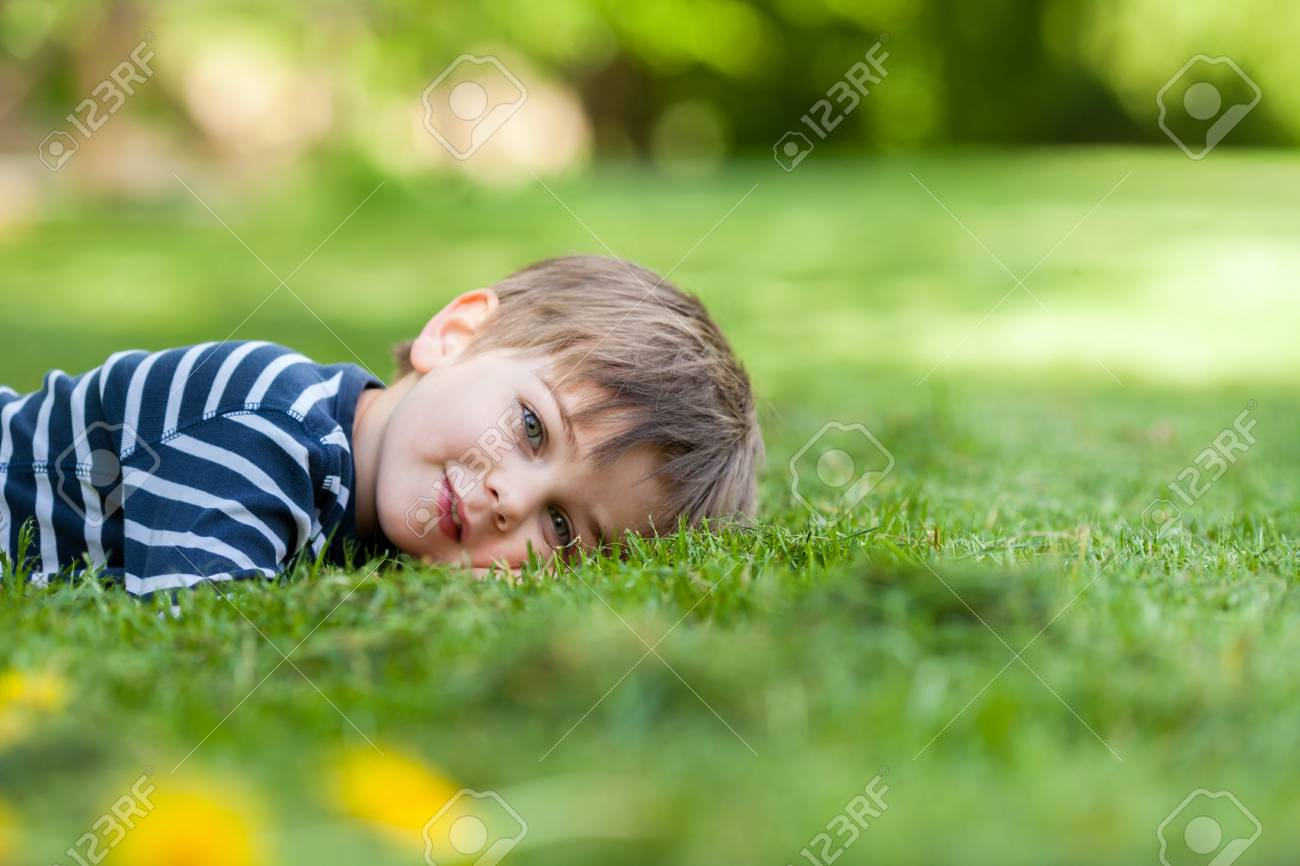 Smiling little boy, lying in the grass, smiling at the camera,