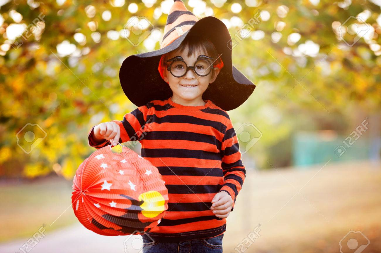 cute boy in the park with halloween costume hat and glasses having fun autumn