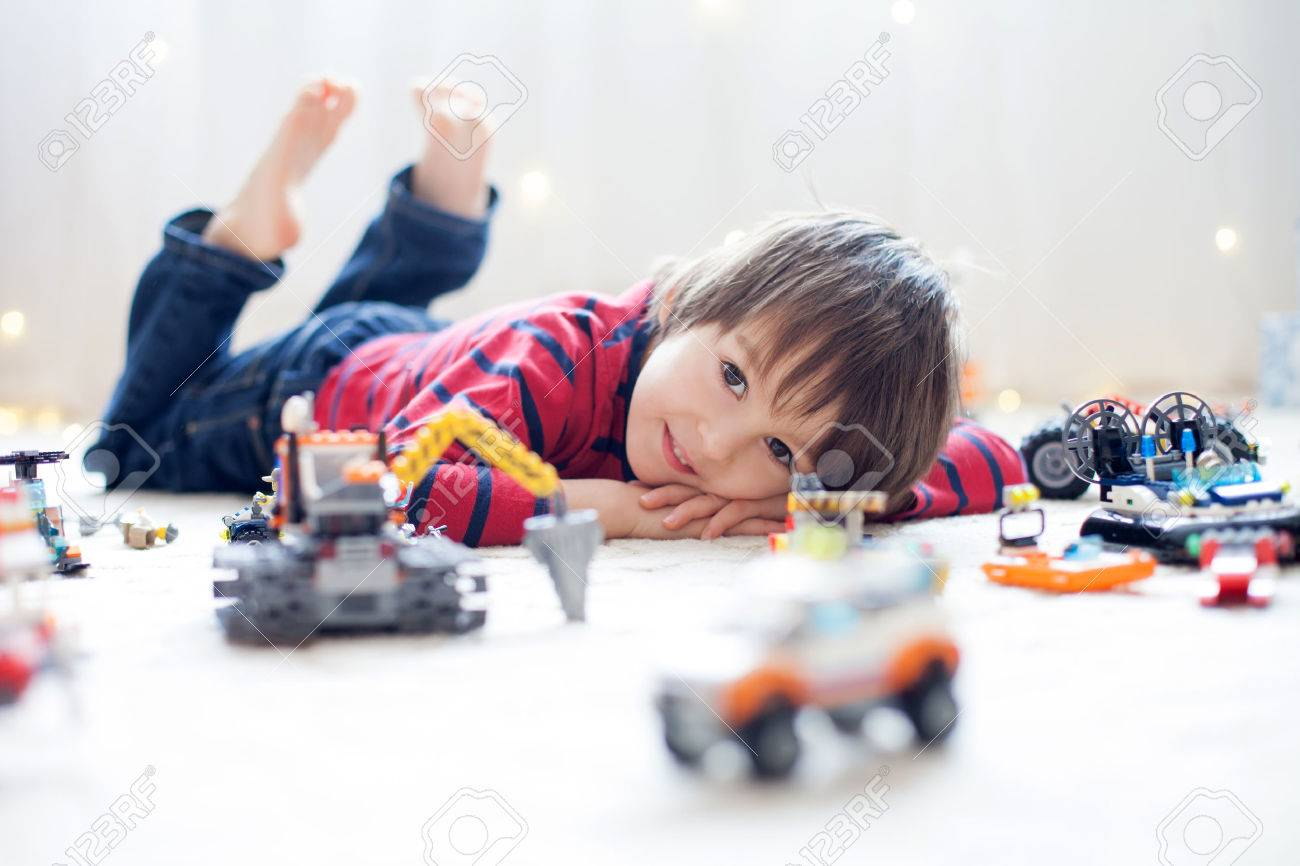 Little child playing with lots of colorful plastic toys indoor, building different cars and objects - 50549377