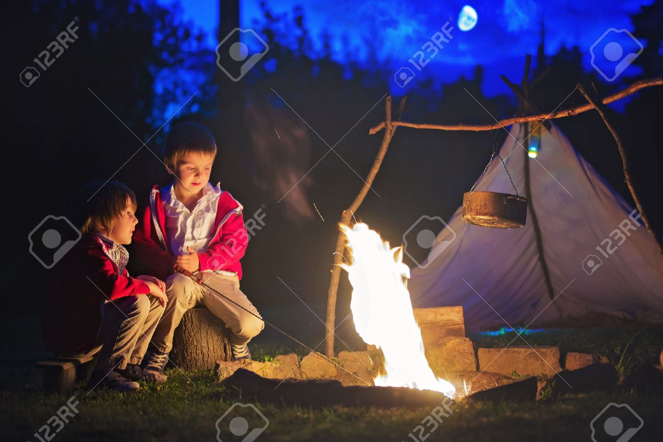 Two sweet boys sitting around the c&fire after sunset listening scary stories Stock Photo & Two Sweet Boys Sitting Around The Campfire After Sunset ...