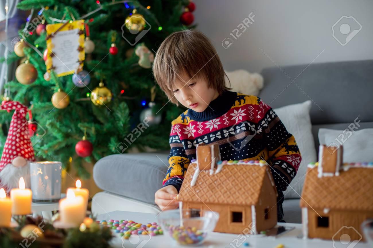 Decorazioni Natalizie Per La Camera adorabile bambino, ragazzo, la decorazione le camere prescolare pan di  zenzero per natale a casa, l'albero di natale dietro di loro, avvento  candele