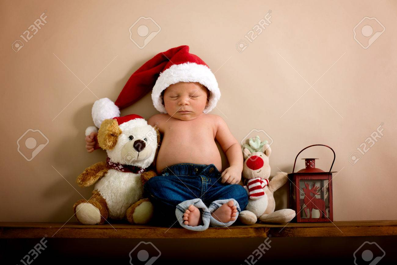 65493c16336 Newborn Baby Boy Wearing A Christmas Hat And Jeans
